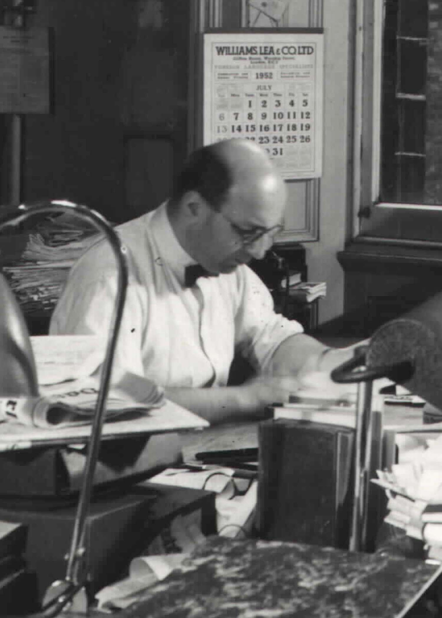 Black and white photograph of man sitting at desk