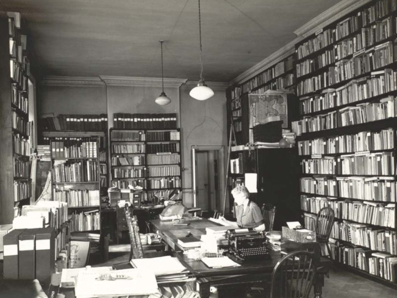 Woman at a desk surrounded by bookshelves in the Library's Reading Room