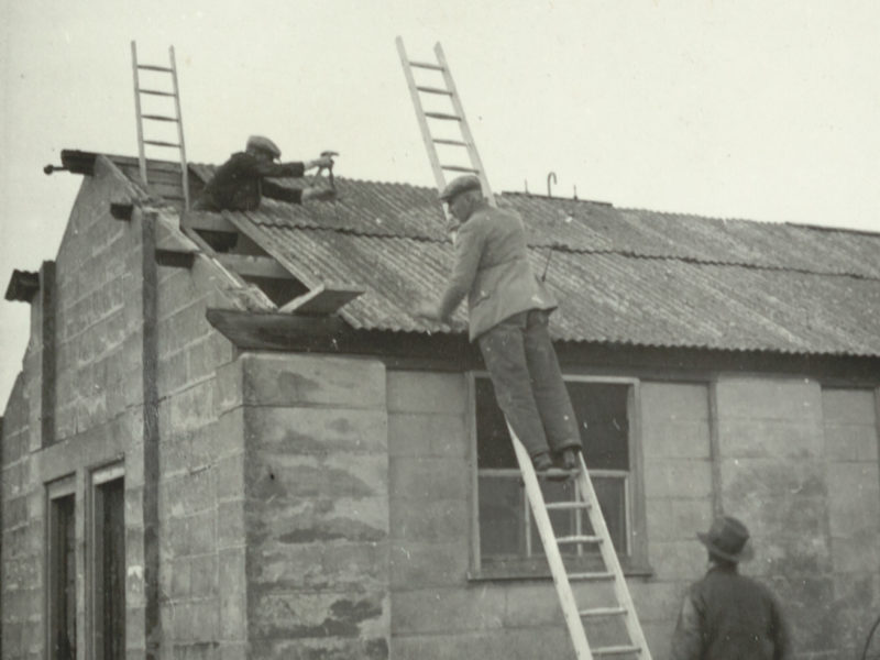 Black and white photograph of men working on roof