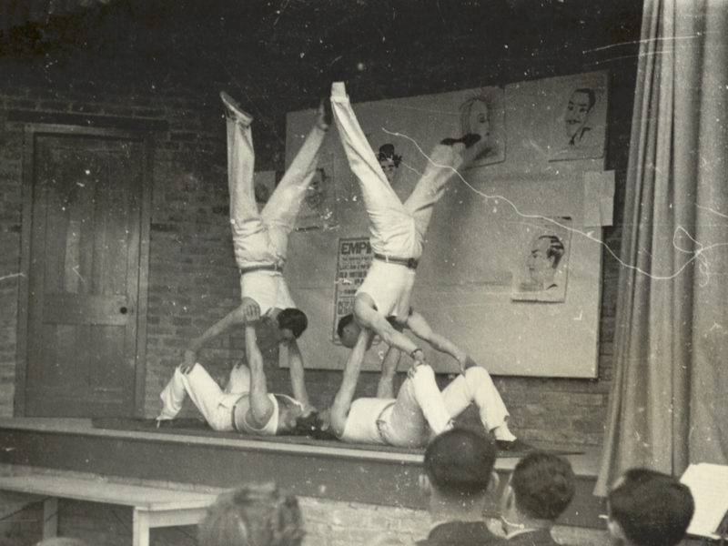 Black and white photograph from audience watching acrobats on stage