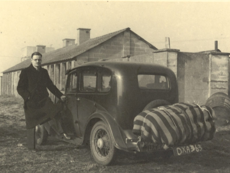 Black and white photograph of man standing next to old car
