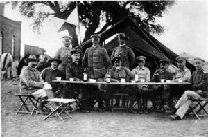 Group of men dressed in military uniform outside a tent