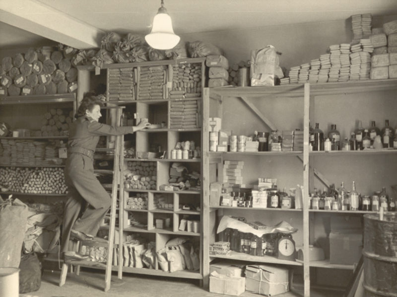 Black and white picture of lady on ladder in store room