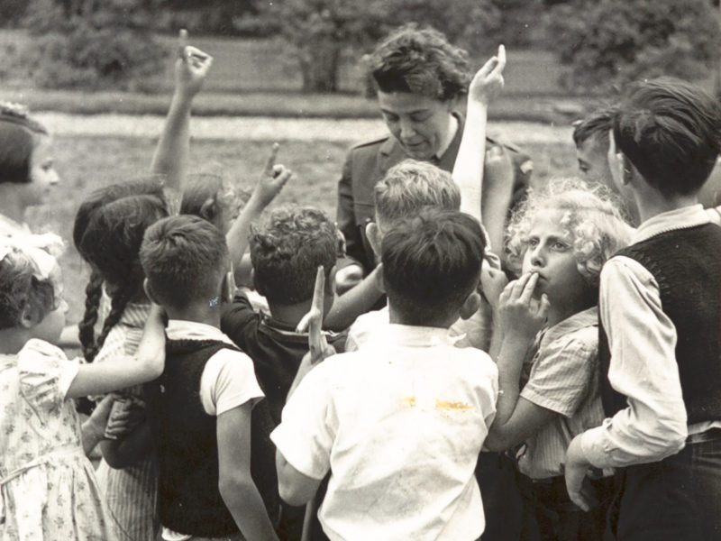 Black and white photograph of children with hands in the air
