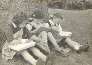 Black and white photograph of three girls sitting and reading
