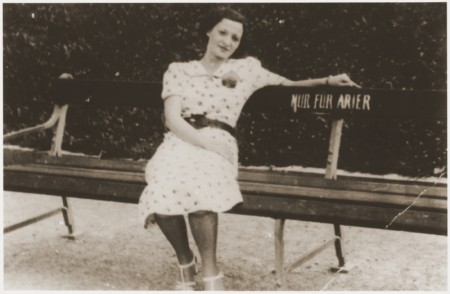 Black and white photograph of lady sitting on bench