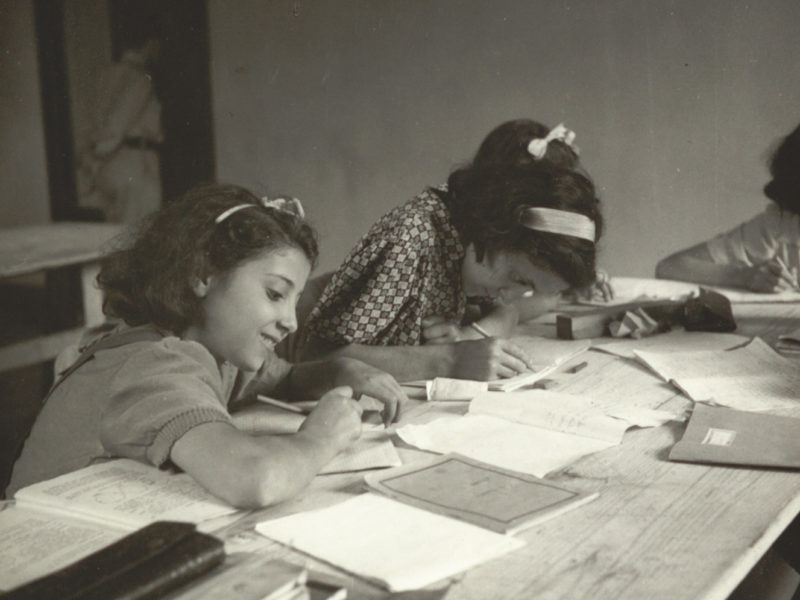 Black and white photograph of girls writing