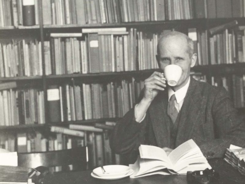 Black and white photograph of man drinking cup of tea in library