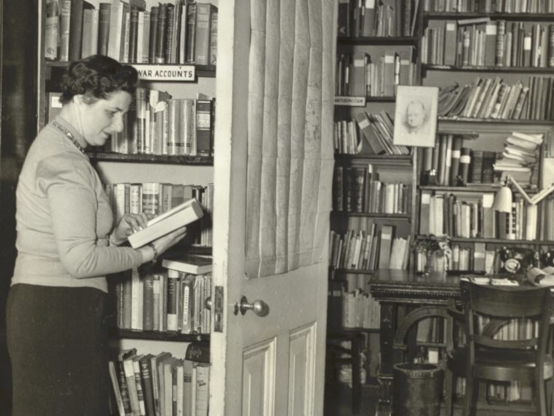 Black and white photograph of lady standing in library reading