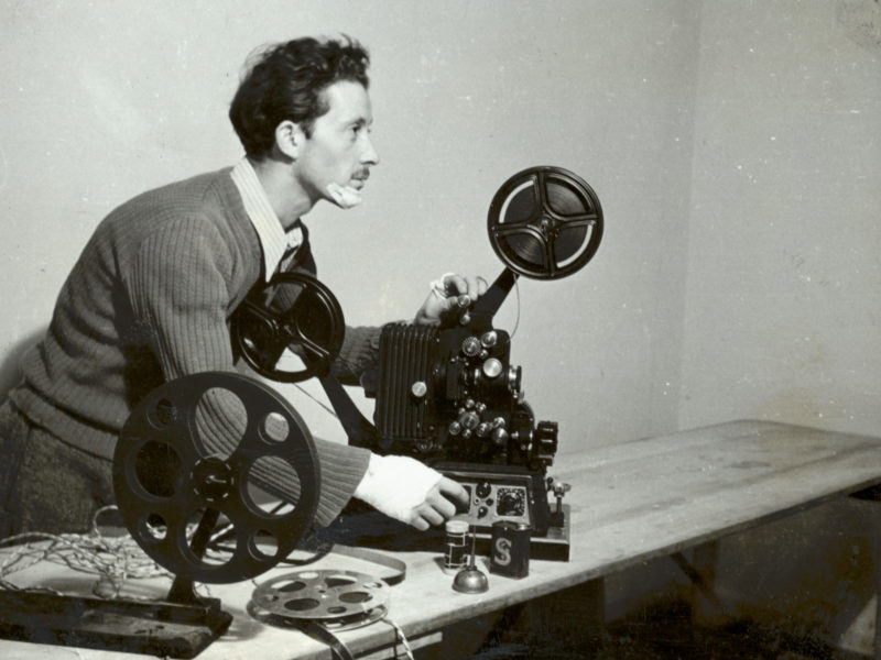Black and white photograph of man with projector