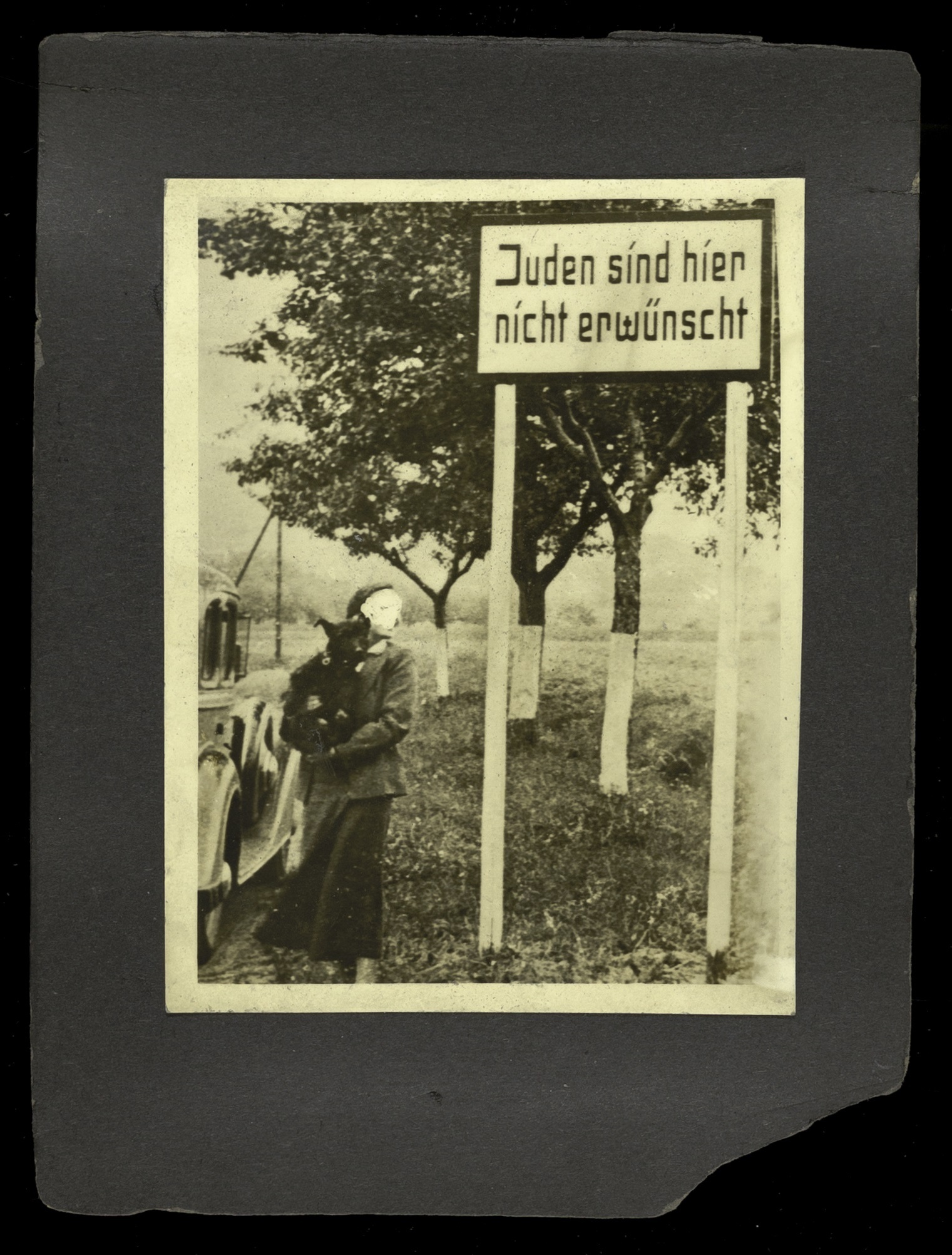 Woman posing next to antisemitic sign