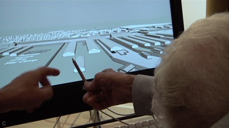 An elderly person uses a stylus on a digital screen showing buildings in a field