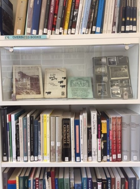 Four books on display in a glass cabinet amongst shelves of books stacked on the shelf