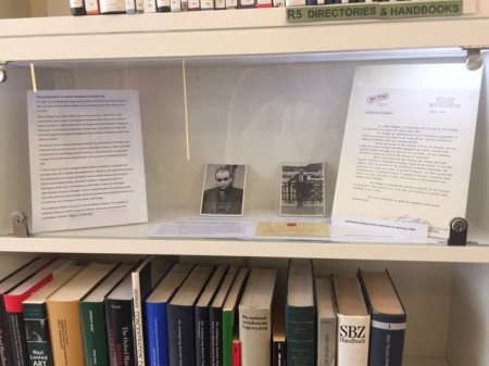 Two small photographs on display next to a typed letter and exhibition text