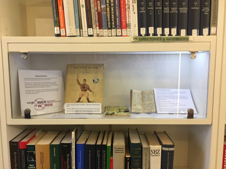 Open journal, illustration and document on display on a bookshelf