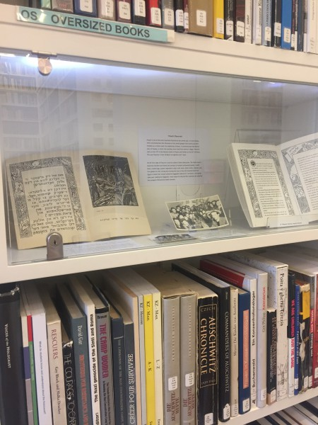 Open books on Purim and Pesach on display behind glass
