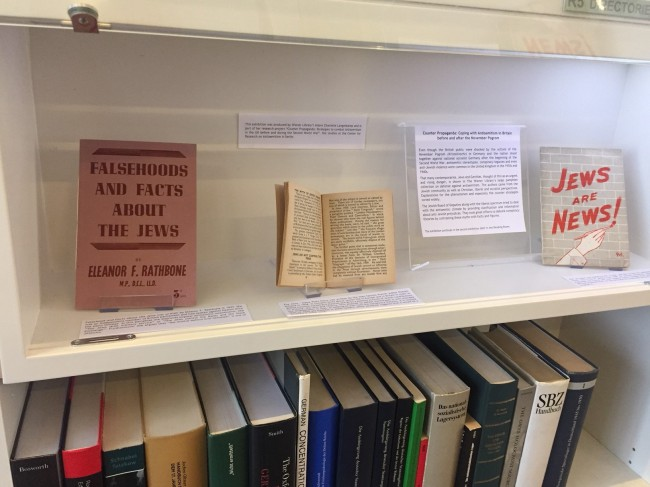A pink covered book reading falsehoods and facts about jews on display with other documents and books