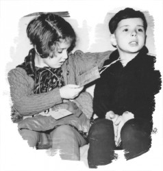 Two young children in coats wearing luggage tags around their neck