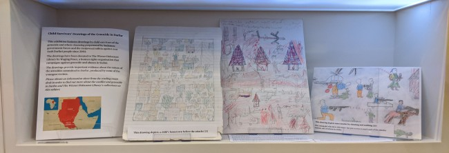 Three children's drawings of varying scenes on display with exhibition text