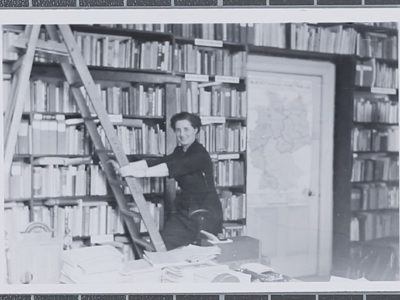 Woman standing in the library next to a stepladder