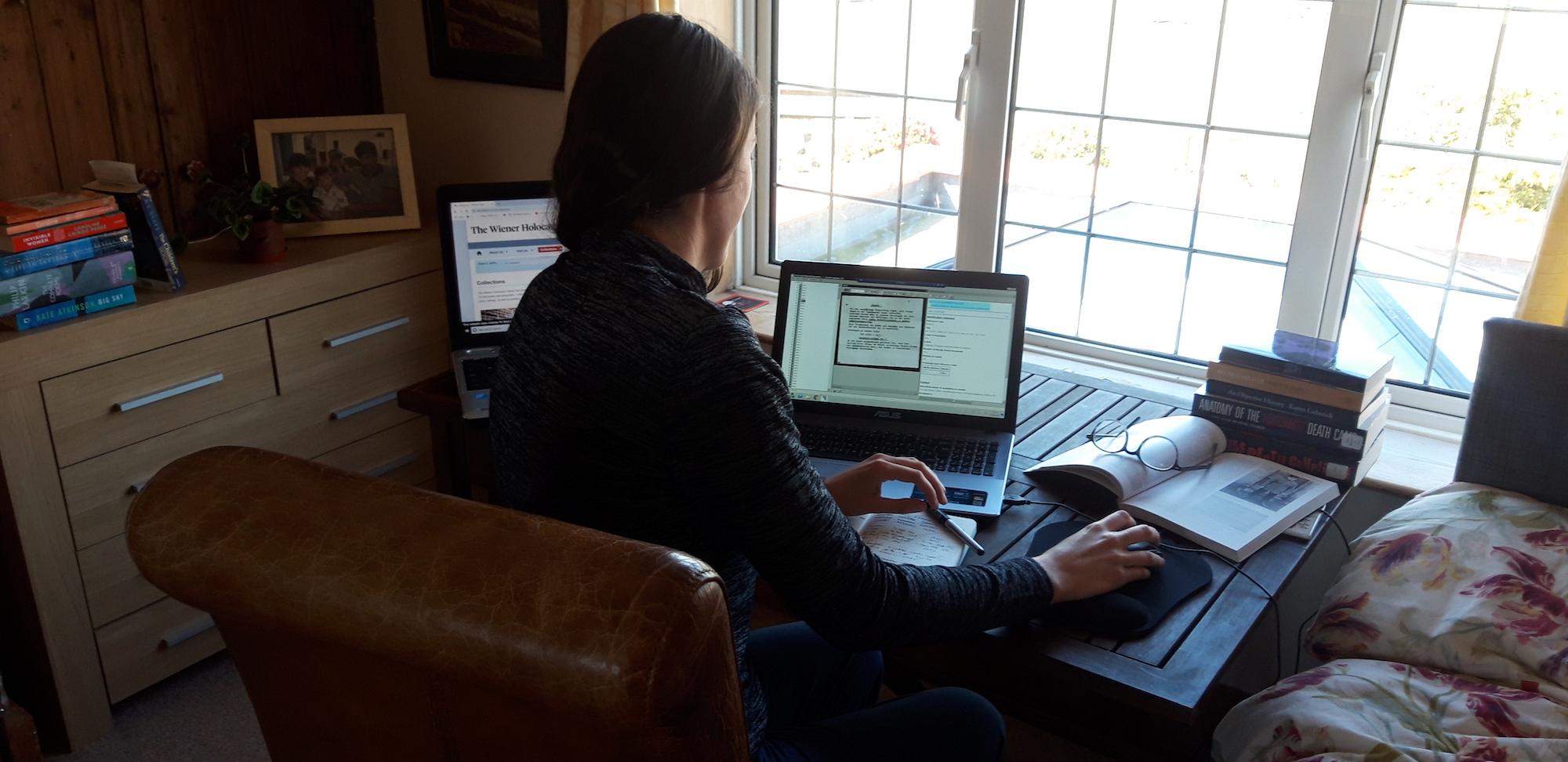 ITS Archive Researcher Elise Bath sits at a desk