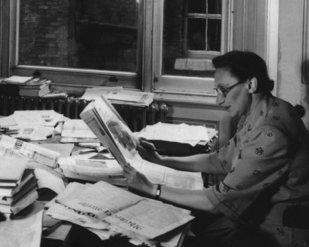 A woman wearing glasses reads a book at a desk covered in books and papers
