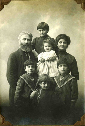 Family photograph of assumed parents with five children, the smallest girl in the centre wearing a big dress