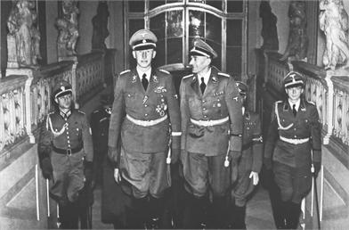 A group of soldiers in uniform walk up a staircase with statues either side.