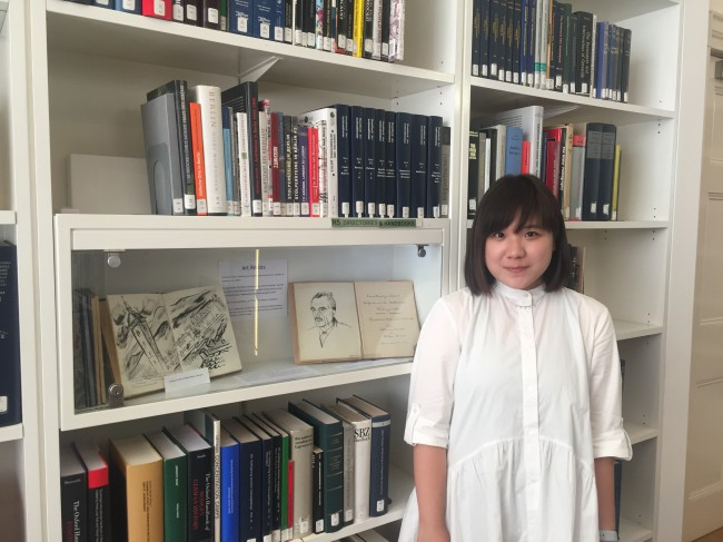 A woman with bobbed brown hair and white shirt dress stands in front of bookcase and display cabinet