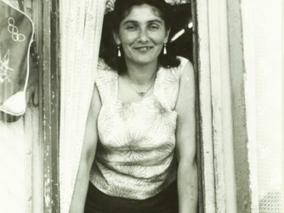 A woman with short dark hear wearing a white top leans out of a window, smiling