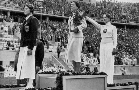 Three women stand on podiums in a stadium at a sporting event
