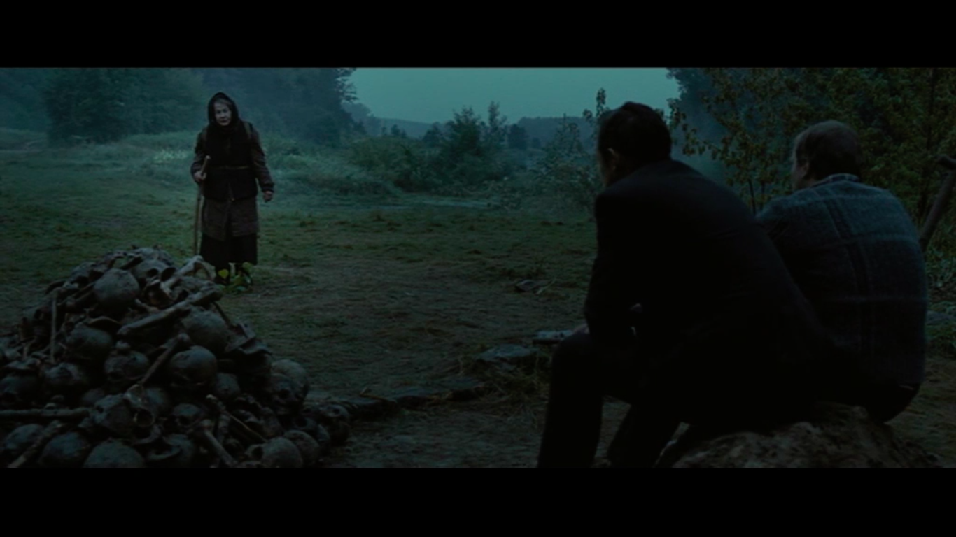 Still taken from 'Aftermath' (2012). Shows an old woman approaching two men with their backs to the screen