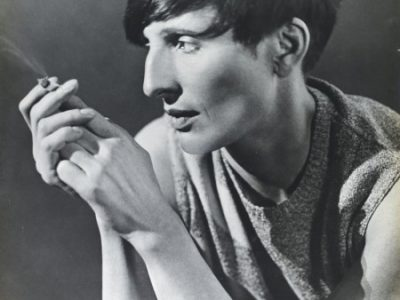 A woman with a stylish bowl cut and angular cheekbones leans on her elbows smoking a cigarette in a tshirt with rolled up sleeves