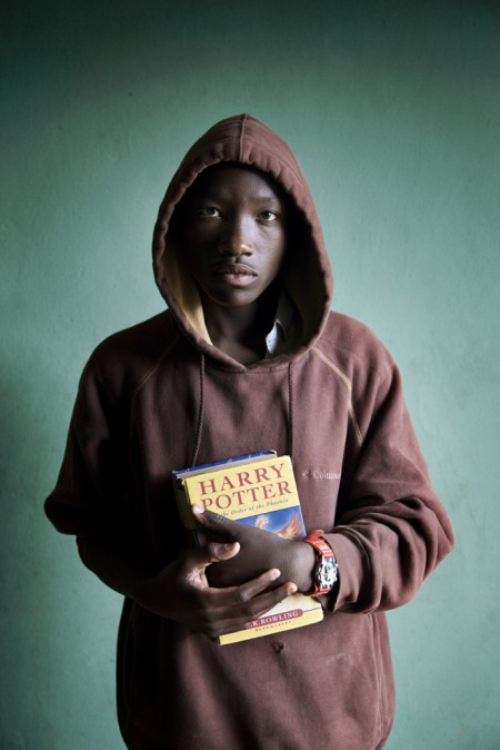 A young adult male in burgundy hoody, holding a copy of Harry Potter