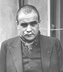 A shaved man in a shirt and jacket with bandages stuck under his nose. He looks sad.
