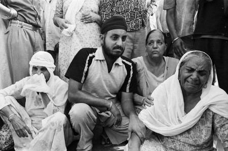 A group of people sitting down in a crowd, visibly upset with some crying