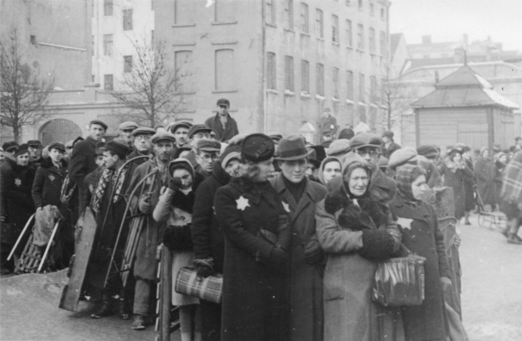 Crowd of Jews - one is wearing a visible Yellow Star.