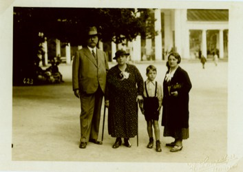 A family of a man, two women and child in formal wear pose in front of a tree