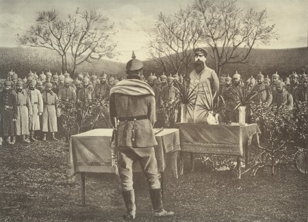 Two soldiers stand behind tables opposite each other in a field, with many other soldiers in the background