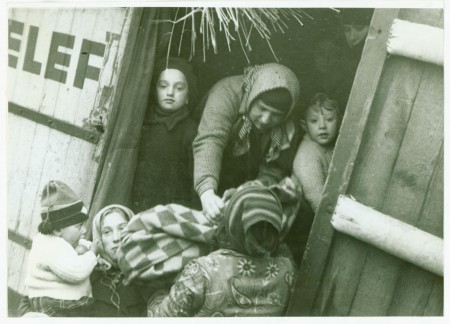 Children look on through a doorway as blankets are passed between two people