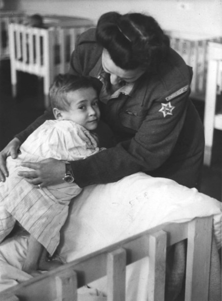 A female soldier leans over to soothe an infant in a hospital bed