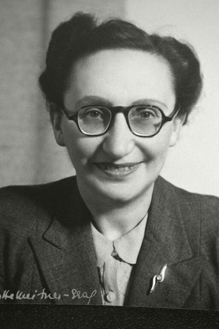 A woman with round glasses and pinned back dark hair