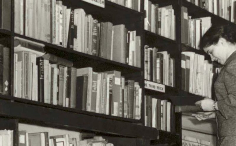 Woman on stepladder reaching books from high shelves