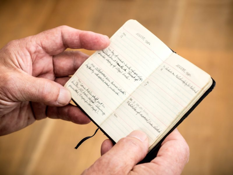 Hands hold a small hand-written diary