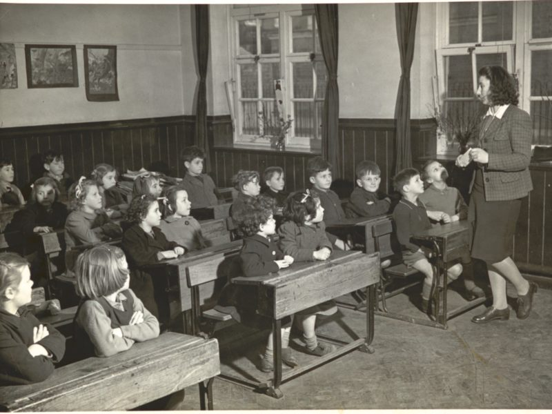 Children sitting in a classroom being taught by a teacher