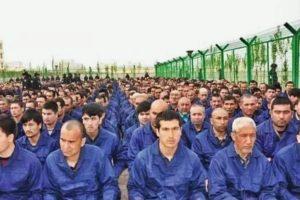 Uyghur men sit in rows inside a detention camp.