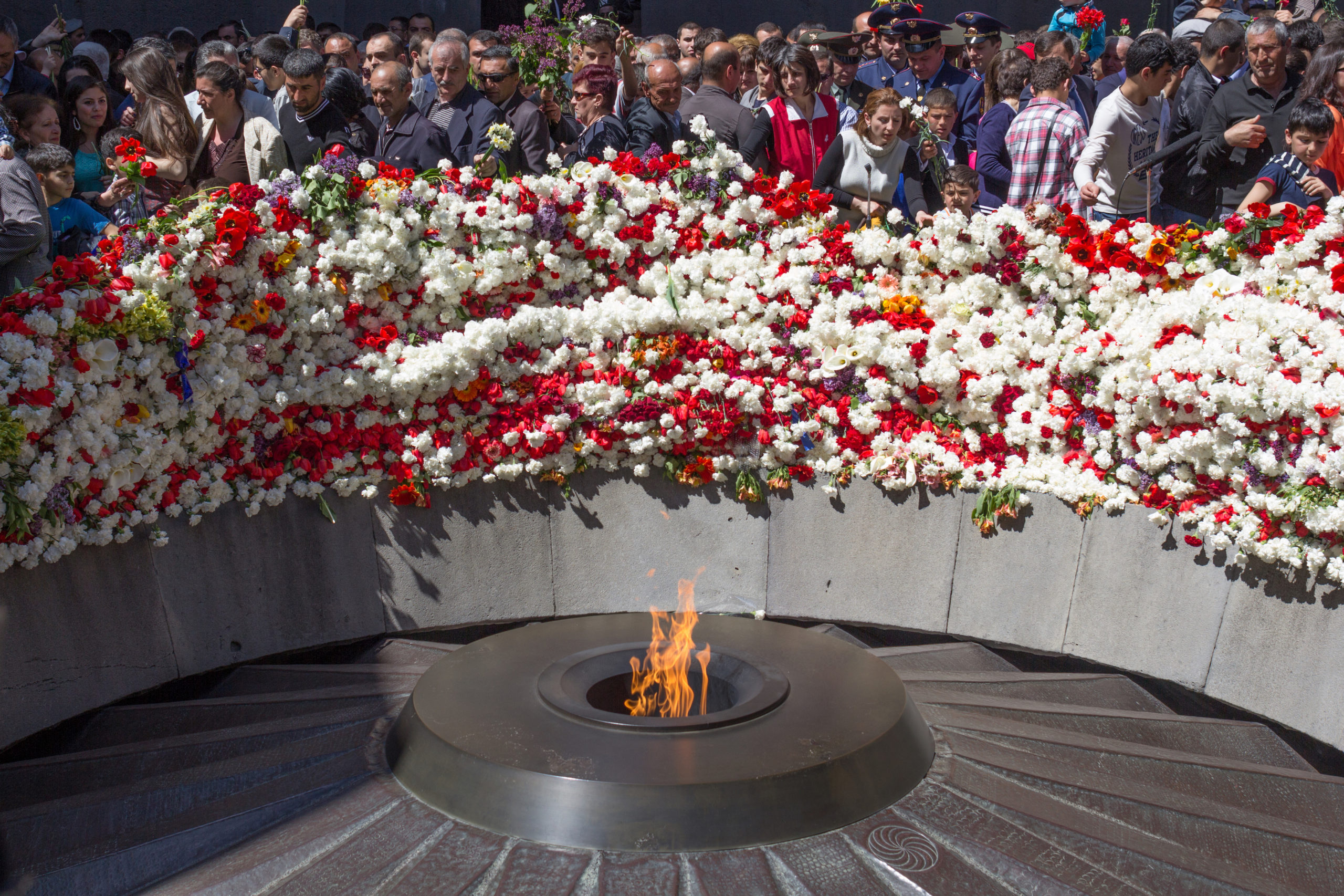 Flowers and people surround a memorial flame in Armenia