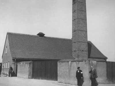 A black and white image of a building with a tall chimney. Two figures stand in the foreground