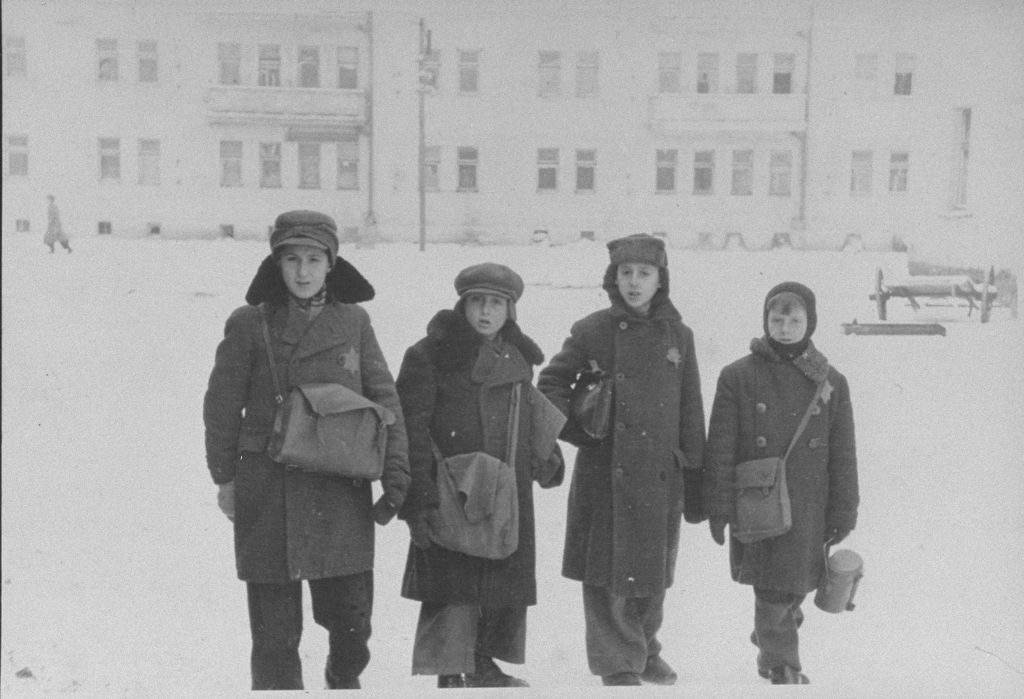 Four schoolboys pictured in the snow within a Nazi ghetto