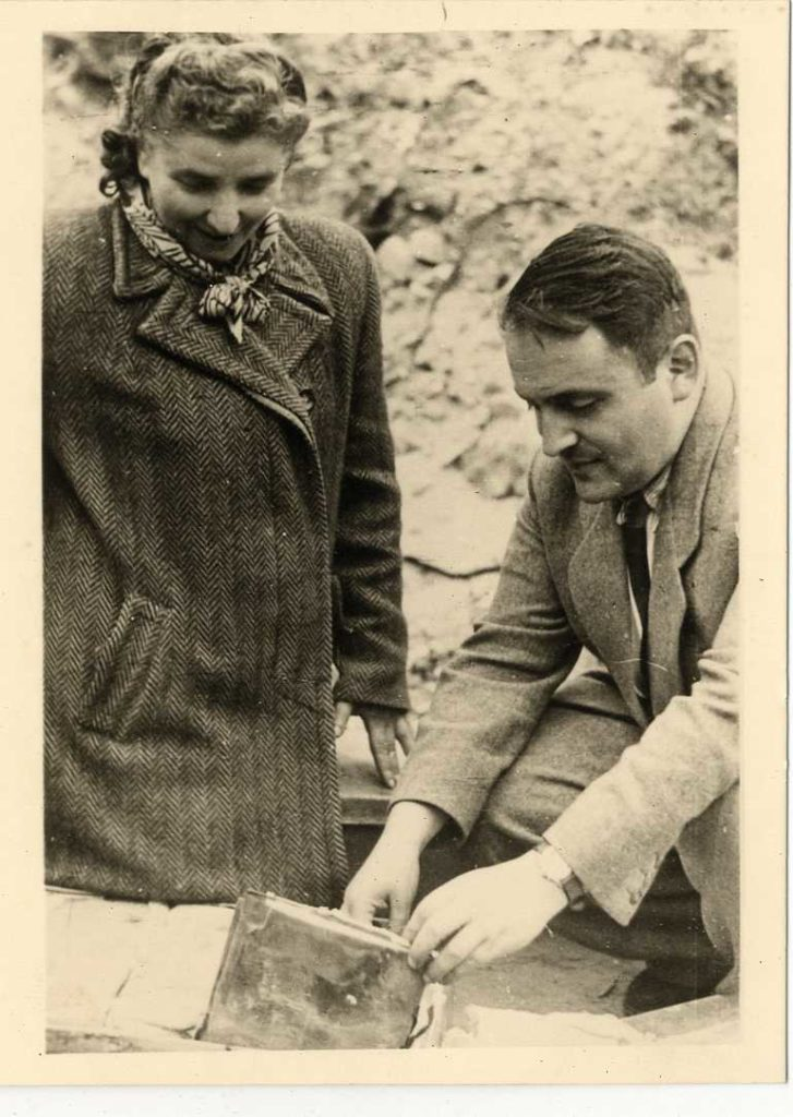 Two people digging up buried archives